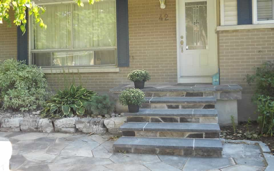 Flagstone and black granite front step, weathered limestone rocks retaining garden beds