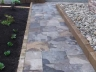 Square cut limestone walkway with gardens, planter box & river rock